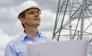 Engineer reviewing plans near electrical tower